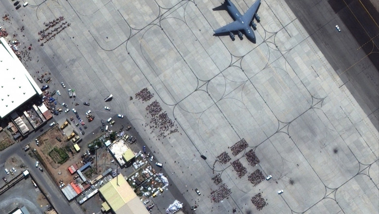 This handout satellite image released by Maxar Technologies shows crowds of people waiting on the tarmac at Kabul's Hamid Karzai International Airport in Afghanistan, with a c17 transport aircraft ready, on August 23, 2021