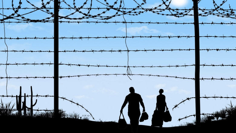 A man and woman are seen in silhouette after breaching a border fence on the southern border of the USA. They have gone through a broken barbed wire f