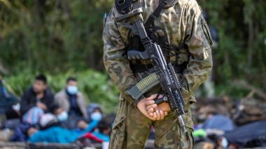 un soldat polonez cu arma în spate păzește migranți afgani de la granița cu Belarusul