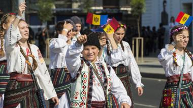 tineri in costume populare defiland in mana cu stegulete ale republicii moldova