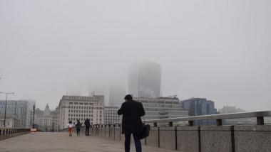 oameni merg pe stradă prin Aer poluat în Londra.