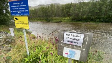 panou improzivat pe malul norvegian al unui rau care avertizează in engleză că este interzisă urinarea in directia rusiei