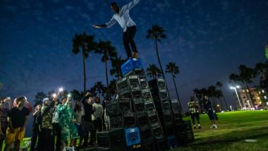 un barbat pe punctul de a cădea de la inaltime noaptea de pe o piramida de lazi din plastic