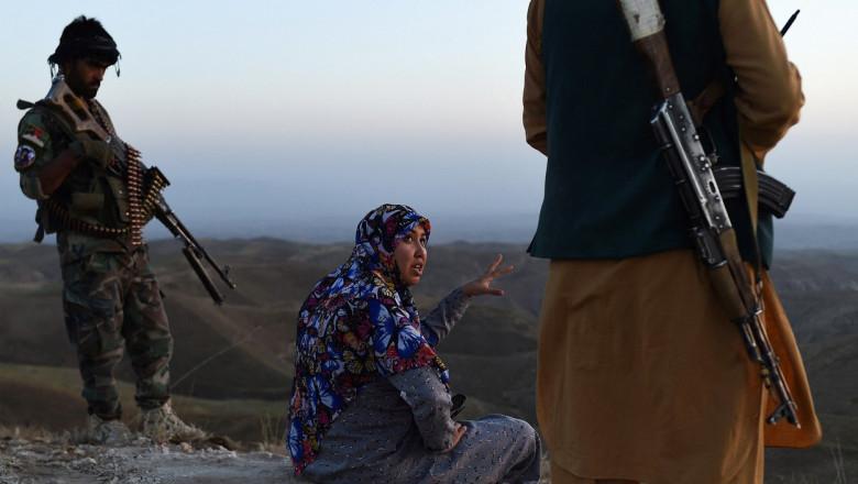 O femeie cu capul acoperit vorbește cu bărbați înarmați