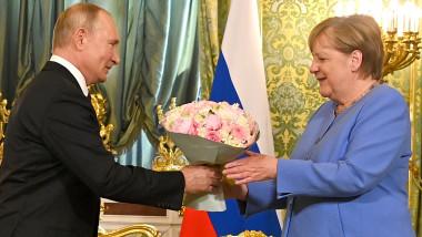 Angela Merkel primește un buchet de flori de la Vladimir Putin în ultima sa vizită oficială la Moscova.