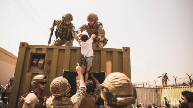 copil ridicat de soldati sus pe un container pe aeroportul din kabul
