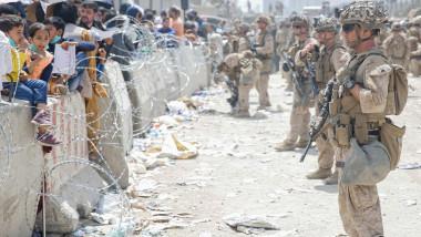 afgani la zidul de protectie de pe aeroportul din kabul fata in fata cu soldati americani