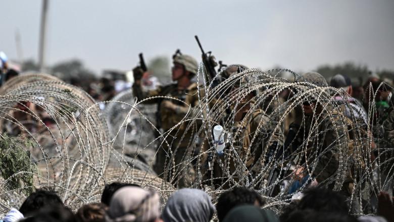 soldati americani printre sarma ghimpata cu arme ridicate in aer