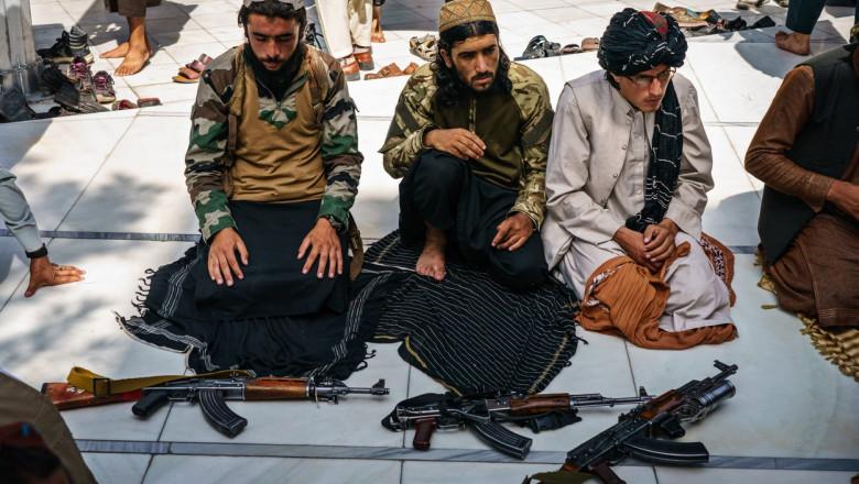 Talibani cu puști kalașnikov lângă picioare
