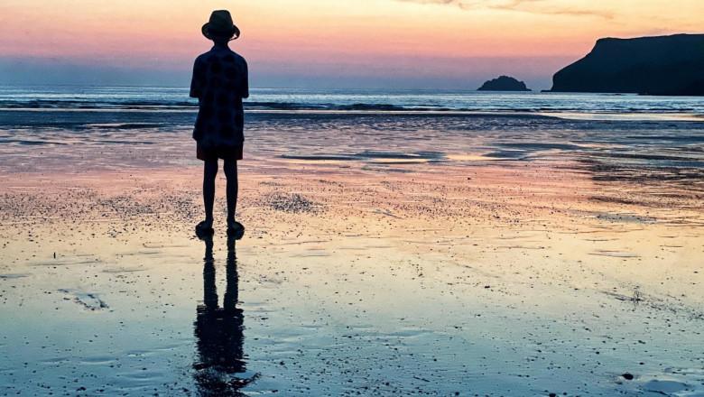 un copil priveste apusul de soare pe o plaja din cornwall