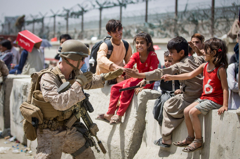 A Marine with Special Purpose Marine Air-Ground Task Force-Crisis Response-Central Command (SPMAGTF-CR-CC) plays with children waiting to process during an evacuation at Hamid Karzai International Airport, Kabul, Afghanistan, Aug.  20. US service members