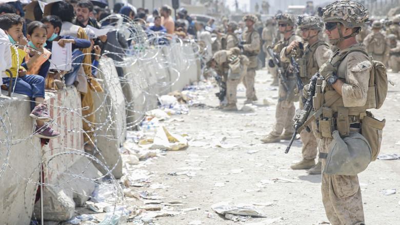 Soldați americani în fața unui zid cu sârmă ghimpată și civili afgani pe cealaltă parte