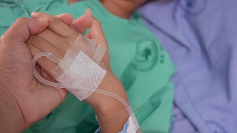 copil cu perfuzie tinut de mana pe patul de spital