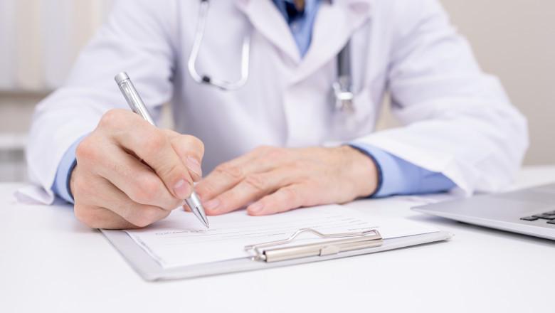 Un medic scrie o rețetă.