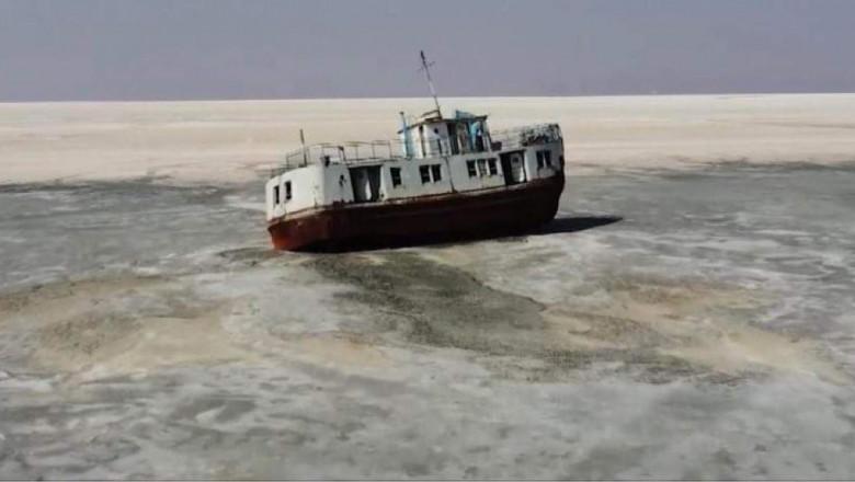 Ilustrație cu un feribot blocat pe lacul Urmia care se usucă.