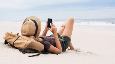 tanata cu palarie ple plaja, cu telefonul in mana
