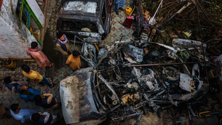 Relatives and neighbors of the Ahmadi family gathered around the incinerated husk of a vehicle targeted and hit earlier Sunday afternoon by an American drone strike, in Kabul, Afghanistan