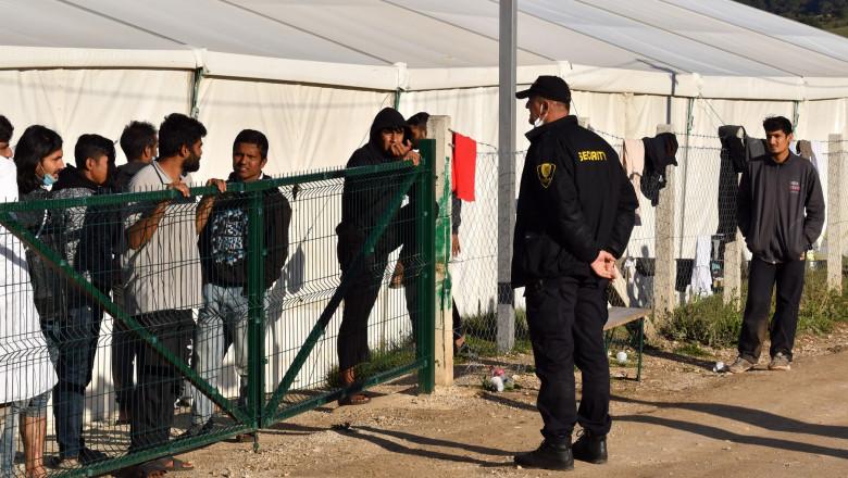 un agent de securitate privește în spatele unui gard la refugiați