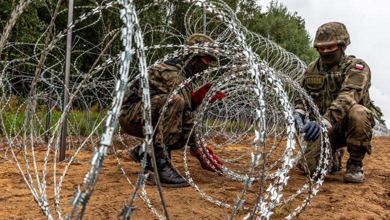 soldați polonezi întind sârmă ghimpată sub formă de barieră pentru a opri refugiați în august 2021