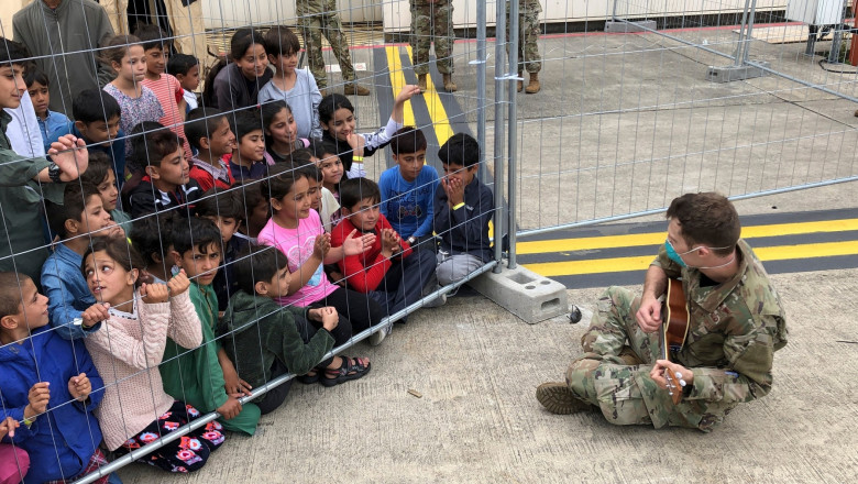 Air Force airman plays the ukulele for Afghan children to keep them entertained at Ramstein Air Base August 24, 2021