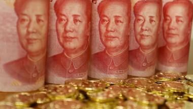 bancnote de 100 de yuani aliniate langa monede