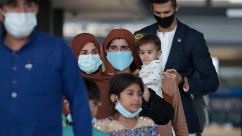Refugiați afgani cu măști de protecție într-un aeroport după evacuarea din Kabul