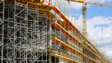 bloc in constructie cu schele si macara