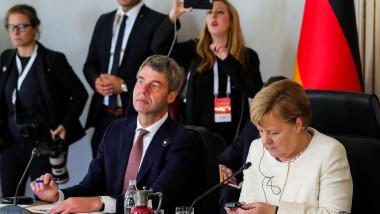 Angela Merkel și Jan Hecker(în stânga imaginii), pe vremea când acesta era consilier de politică externă al cancelarului german, în timpul unui summit din 2018 al liderilor din Turcia, Rusia, Germania și Franța privind situația din Siria.