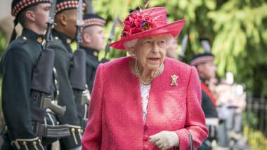 Regina Elisabeta a II-a îmbrăcată în roz trece pe lângă militari