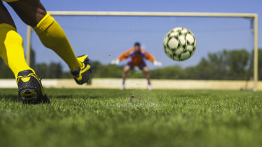 Un jucător execută o lovitură de la 11 metri.