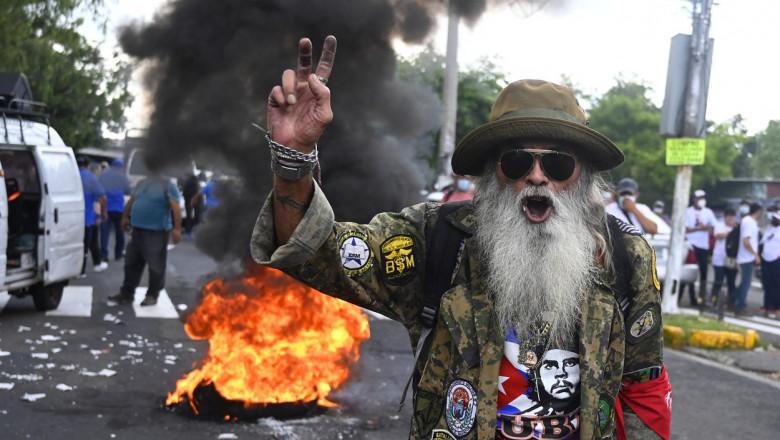 Bărbat cu barbă albă, pălărie și ochelari de soare face semnul victoriei în timp ce în spate ard cauciucuri