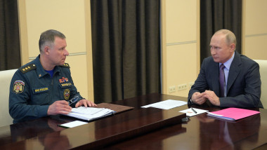 Russian President Vladimir Putin and Emergencies Minister Yevgeny Zinichev attend a meeting on the situation in regions hit by floods and wildfires via a teleconference call at the Novo-Ogaryovo state residence outside Moscow on April 27, 2020