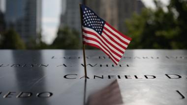 mini steag american într-o gravură a numelui uneia dintre victimele de la atacurile terorist din 11 septembrie 2001