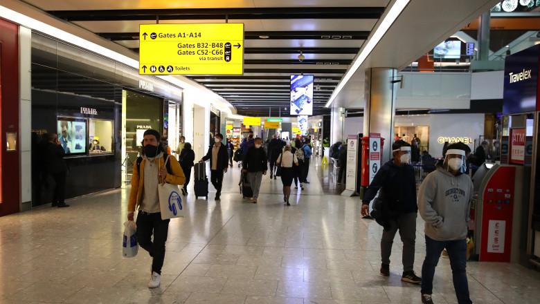 Oameni care poartă mască în aeroport.