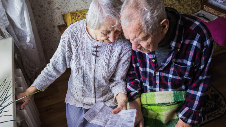 doi batrani cu mana pe calorifer se uita la o factura