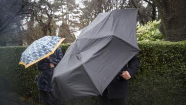 oameni cu umbrele pe strada