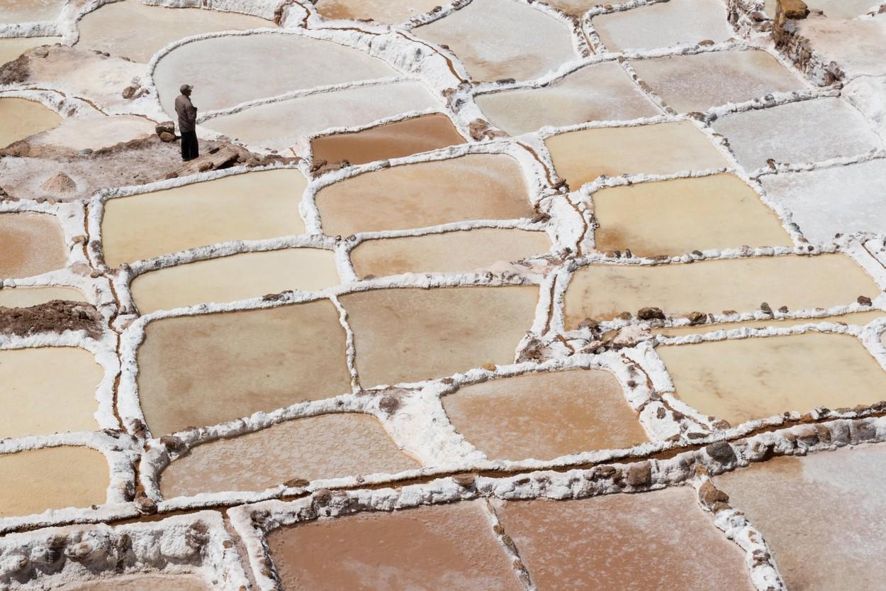 Single worker tends to his family salt plot at the Maras salt mines near Cusco, Peru