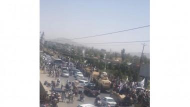 mulțime și convoi de vehicule blindate pe străzile din Kandahar