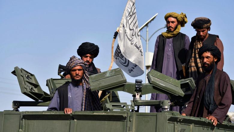 Talibani cu un steag al emiratului islamic al Afganistanului pe un vehicul militar blindat