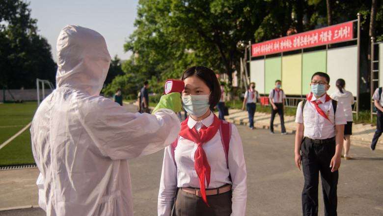 Un lucrător sanitar nord-coreean, în costum de protecție complet, ia temperatura unei eleve în Phenian
