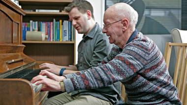 Un bătrân din Marea Britanie cu demență încearcă să cânte la pian alături de fiul său.