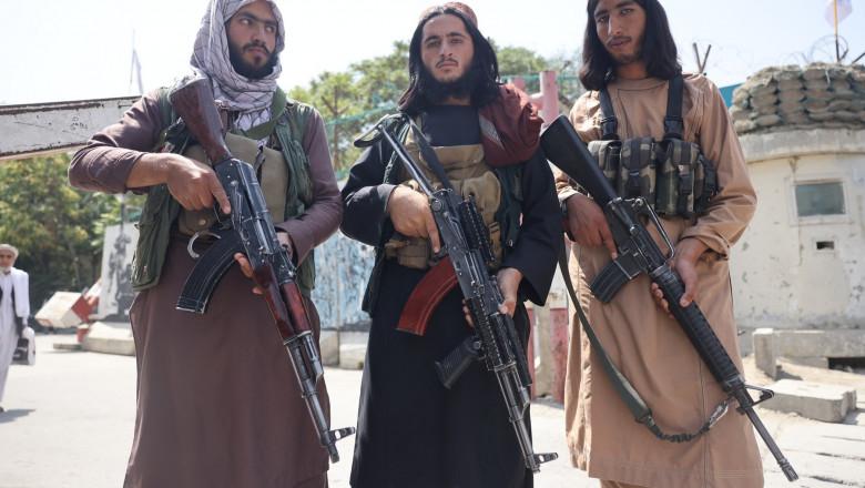 Bărbați afgani cu puști kalașnikov în mâini