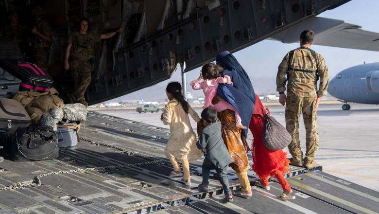 femeie cu copii care se urca intr-un avion militar