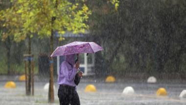 femeie cu umbrela prin ploaie