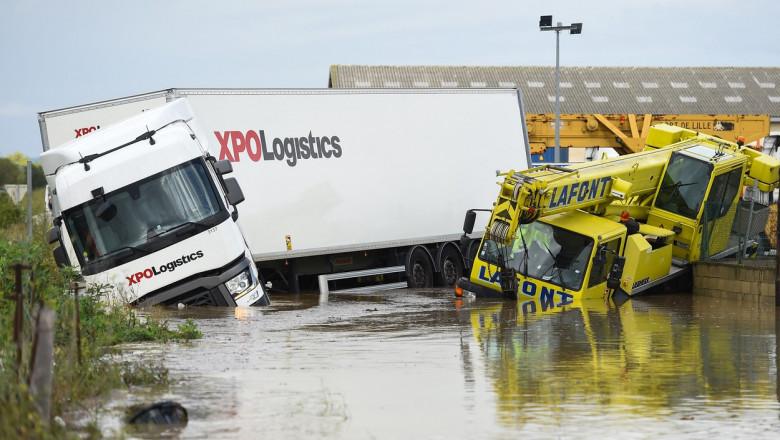Un camion este rasturnat intr-o parte alaturi de un utilaj in apa