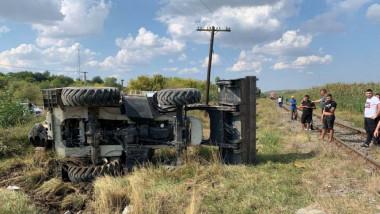 Excavatorul lovit de tren a fost răsturnat pe camp, oamenii se uita