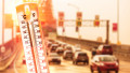 Thermometer in front of cars and traffic during heatwave