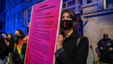 O femeie care ține în mână o pancartă cu mai multe mesaje și poartă o mască neagră de protecție cu fulger roșu pe mijloc, un simbol al protestelor împotriva înăspririi legii avortului din Polonia, participă la un protest pentru libertatea de alegere în fața Ministerului Educației din Varșovia