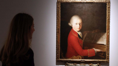 A woman looks at a painting showing a portrait of Austrian composer Wolfgang Amadeus Mozart at the age of 13, dated from 1770 and attributed to Italian painter Giambettino Cignaroli