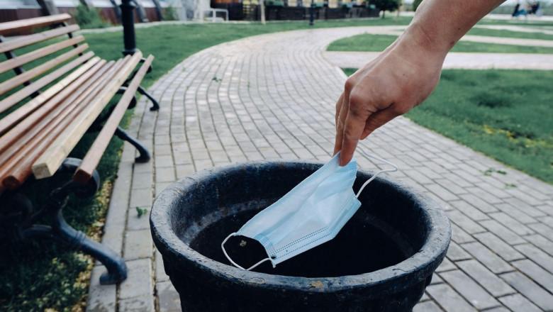 o mână care aruncă o mască de protecție la coșul de gunoi pe o străduță de parc